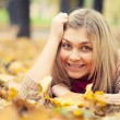 Young woman laying down on the ground in autumn park — Стоковая фотография