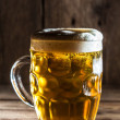 Mug of beer on wooden background — Lizenzfreies Foto
