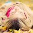 Young woman laying down on the ground in autumn park — Stock Photo