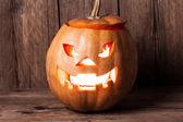Scary jack-o-lantern on wood — Stock Photo