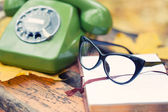Green vintage phone, book and glasses on bench in autumn park — Stock Photo