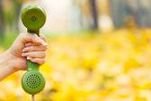 Hand holding vintage phone receiver in autumn park — Stok fotoğraf
