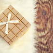 Gift box with white fur on wooden background — Foto Stock