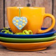 Cup of tea with three plates and spotted heart shaped label — Stock Photo #36514637
