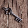 Single key on wooden background — Stock Photo