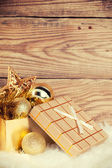 Gift box with christmas decoration on wooden background — Stock Photo