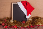 Blank blackboard with Santa hat and christmas decoration — Stock Photo