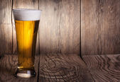 Mug of beer on wooden background — Stock Photo