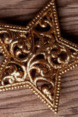 Golden christmas star on wooden background — Stock Photo