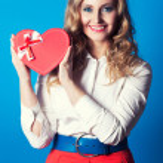 Woman holding heart-shaped box — Stock Photo