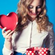 Woman holding heart-shaped box — Stock Photo #40037165