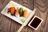Fresh sushi on wooden background — Stock Photo