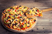Delicious italian pizza served on wooden table — Stock Photo