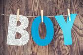 Boy word hanging on clothesline — Stock Photo