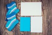 Knitted baby socks and blank notes — Stock Photo
