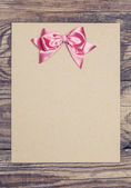 Pink bow on old paper — Stock Photo
