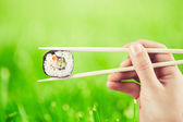 Hand with sushi roll — Stock Photo