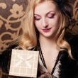 Retro woman holding a gift box — Stock Photo