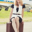 Woman sitting on old suitcase — Stock Photo