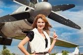 Woman posing against plane — Stock Photo