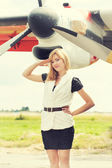 Beautiful woman posing against plane — Stock Photo