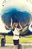 Beautiful woman posing near plane — Stock Photo