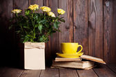 Roses in pot, tea cup and books — Stock Photo
