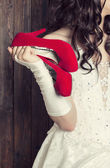 Bride holding a pair of red shoes — Stock Photo