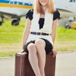 Woman sitting on old suitcase against plane — Stock Photo #50499369