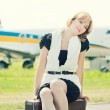 Woman sitting on old suitcase against plane — Stock Photo #50499373