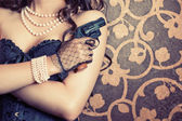 Woman wearing black corset and pearls and holding a gun — ストック写真