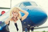 Woman posing near plane — Stock Photo