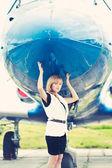 Vrouw poseren in de buurt van vliegtuig — Stockfoto