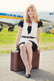 Woman sitting on old suitcase against plane — Stock Photo
