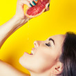 Woman squeezing juice from grapefruit on her lip — Stock Photo #50500473