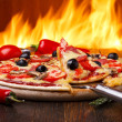 Hot pizza with oven fire on background — Stock Photo #13759210