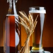Beer bottle and mug with wheat on wooden table still life — ストック写真