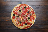 Hot pizza on wooden table — Stock Photo