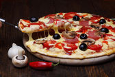 Hot pizza with melting chesse on lifter — Stock Photo