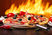Hot pizza with oven fire on background — Stock Photo