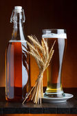 Beer bottle and mug with wheat on wooden table still life — Stockfoto