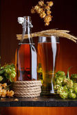 Beer with hop and wheat on wooden table still life — Stock Photo