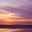 Stock Photo: Sunset on seduring ebb with small fishermboat on horizon
