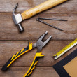 Construction instruments on wooden table - sandpaper, pliers, measuring tape, hammer, nails — Stock Photo #27196107