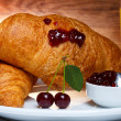 Fresh baked croissants with cherry jam and juice — Stock Photo #27196131