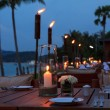 Outdoor restaurant tables, dinner setting on the beach at evening — Stock Photo #27196305