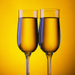 Two champagne flute glasses on yellow background — Stockfoto