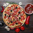 Hot pizza on rustic wooden table with ingredients and cutter — Stock Photo