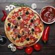 Hot pizza on rustic wooden table with ingredients and cutter — Stock Photo #27196461
