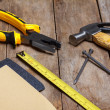 Construction instruments on wooden table - sandpaper, pliers, measuring tape, hammer, nails — Stock Photo